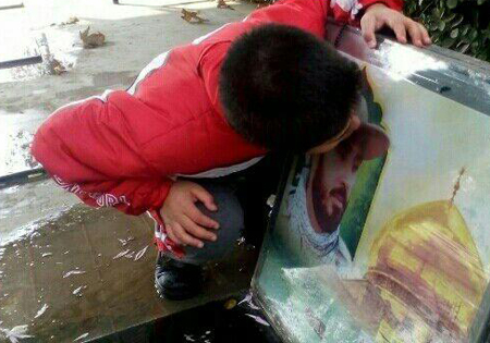 بوسه دلتنگی فرزند شهید بر عکس مزار پدر